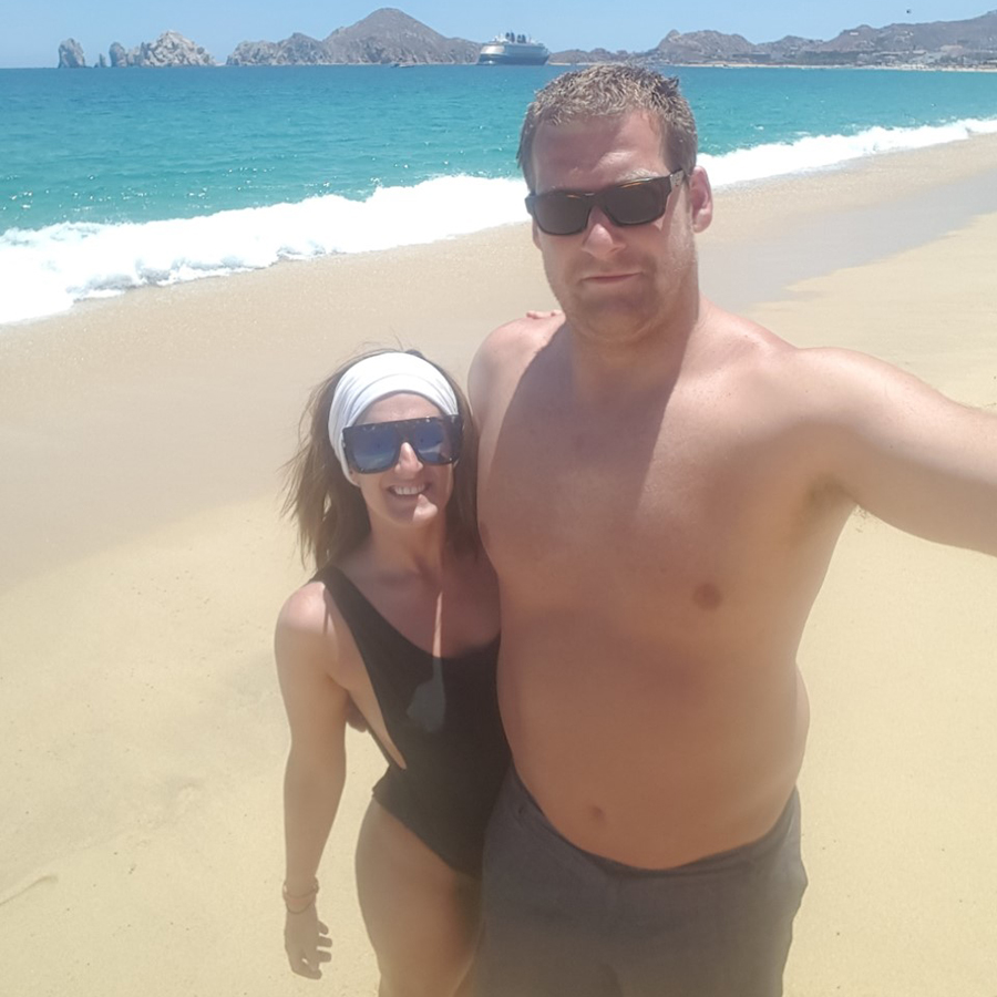 Sirena and Kevin's wedding at the Hotel Riu Santa Fe. They are standing on a beach in their swimwear, taking a selfie.