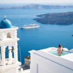 Woman in infinity pool overlooking Santorini Greece