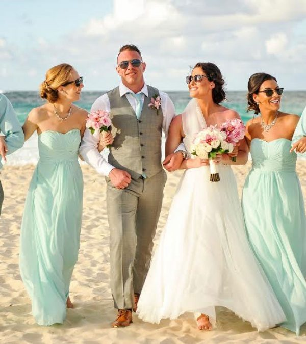 A wedding party walking on a beach in Jamaica